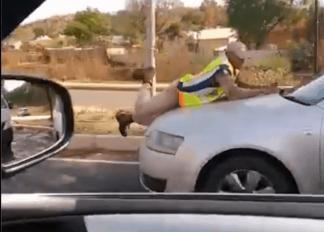 cảnh sát bám vào xe